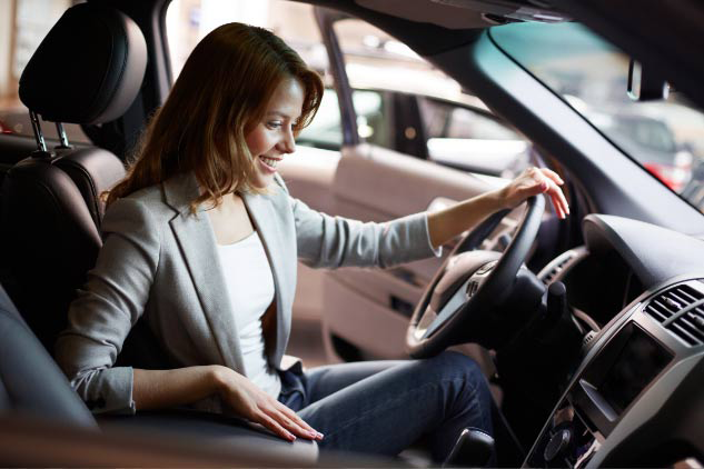 Young woman sitting in the driver's seat of a new car: Looking for a new or used car? Check out Amica's Car Connection
